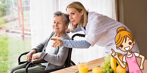 Auxiliaire de vie derrière le fauteuil roulant d'une personne âgée