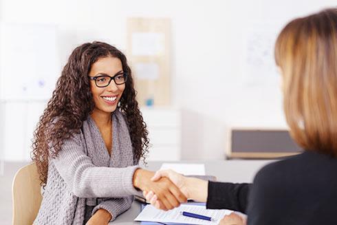Femme souriante serrant la main d'une autre femme