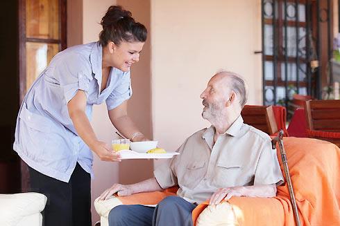 Dame de compagnie servant le petit-déjeuner à une dame âgée